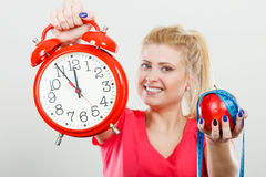 Happy woman holding clock, apple and measuring tape Stock Photo