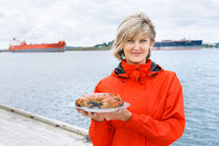 Happy woman holding cooked crab on plate Royalty Free Stock Image