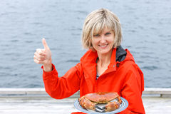 Happy woman holding cooked crab on white plate Royalty Free Stock Image