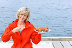 Happy woman holding cooked crab on white plate Stock Photos