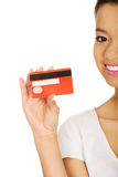 Happy woman holding a credit card. Stock Photos