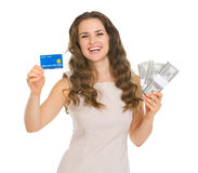 Happy woman holding credit card and dollars packs. Happy young woman holding credit card and dollars packs royalty free stock images