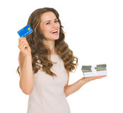 Happy woman holding credit card and money packs Royalty Free Stock Photography