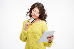 Happy woman holding credit card and using tablet computer Stock Image