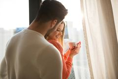 Happy woman holding cup of coffee standing with her boyfriend stock photo