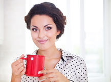 Happy woman holding a cup of coffee wearing pajamas Royalty Free Stock Photography