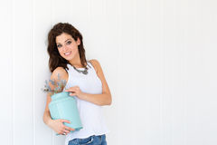 Happy woman holding cute flowers on white wall Stock Photography