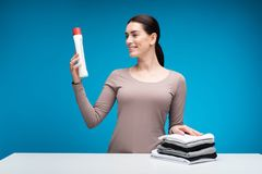 Happy woman holding detergent at table stock photo