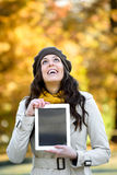 Happy woman holding digital tablet in autumn Royalty Free Stock Photography