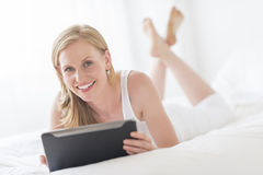 Happy Woman Holding Digital Tablet While Lying On Bed Royalty Free Stock Photo