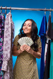 Happy Woman Holding Dollars At The Clothing Rack With Dresses Royalty Free Stock Images