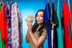 Happy Woman Holding Dollars At The Clothing Rack With Dresses Royalty Free Stock Photography