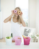 Happy woman holding donuts in front of eyes at kitchen counter Stock Image