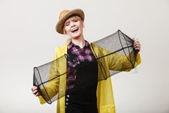 Happy woman holding empty fishing keepnet. Spinning, angling, cheerful fisherwoman concept. Happy woman in yellow raincoat holding empty fishing keepnet, having stock photography