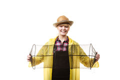 Happy woman holding empty fishing keepnet. Spinning, angling, cheerful fisherwoman concept. Happy woman in yellow raincoat holding empty fishing keepnet, having royalty free stock images