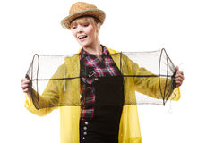 Happy woman holding empty fishing keepnet. Spinning, angling, cheerful fisherwoman concept. Happy woman in yellow raincoat holding empty fishing keepnet, having royalty free stock image
