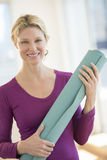 Happy Woman Holding Exercise Mat In Health Club Stock Photo