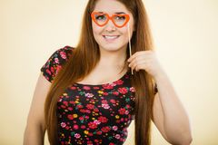 Happy woman holding fake eyeglasses on stick. Having fun. Photo and carnival funny accessories concept Royalty Free Stock Image