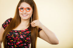 Happy woman holding fake eyeglasses on stick. Having fun. Photo and carnival funny accessories concept Stock Photos