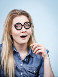 Happy woman holding fake eyeglasses on stick. Happy shocked woman holding fake eyeglasses on stick having fun. Photo and carnival funny accessories concept Royalty Free Stock Photo