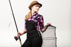 Happy woman holding fishing rod and keepnet. Spinning, angling, cheerful fisherwoman concept. Happy woman in sun hat holding fishing rod and keepnet having fun royalty free stock images