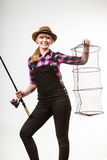 Happy woman holding fishing rod and keepnet. Spinning, angling, cheerful fisherwoman concept. Happy woman in sun hat holding fishing rod and keepnet having fun royalty free stock photos