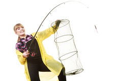 Happy woman holding fishing rod and keepnet. Spinning, angling, cheerful fisherwoman concept. Happy woman in yellow raincoat holding fishing rod and keepnet royalty free stock photography