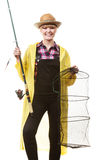 Happy woman holding fishing rod and keepnet. Spinning, angling, cheerful fisherwoman concept. Happy woman in yellow raincoat holding fishing rod and keepnet royalty free stock photo