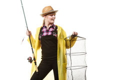 Happy woman holding fishing rod and keepnet. Spinning, angling, cheerful fisherwoman concept. Happy woman in yellow raincoat holding fishing rod and keepnet stock photo