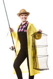 Happy woman holding fishing rod and keepnet. Spinning, angling, cheerful fisherwoman concept. Happy woman in yellow raincoat holding fishing rod and keepnet stock image