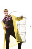 Happy woman holding fishing rod and keepnet. Spinning, angling, cheerful fisherwoman concept. Happy woman in yellow raincoat holding fishing rod and keepnet royalty free stock photos