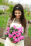 Happy woman holding flower in garden Stock Photography