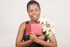 Happy woman holding flowers and a card Stock Photography