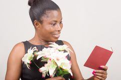 Happy woman holding flowers and a card Stock Images