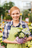 Happy woman holding flowers in greenhouse Royalty Free Stock Photos