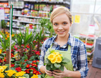 Happy woman holding flowers in greenhouse Stock Images