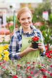 Happy woman holding flowers in greenhouse Stock Photo