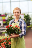 Happy woman holding flowers in greenhouse Royalty Free Stock Images