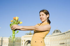 Happy woman holding flowers meeting friend Stock Photo