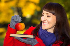 Happy woman holding fresh apple and book in autumnal park, autumn concept Royalty Free Stock Photography