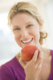 Happy Woman Holding Fresh Apple In Gym Stock Photography