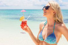 Happy woman holding fresh and tasty cocktail on the beach Stock Image