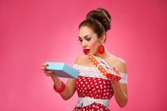 Happy Woman Holding Gift Box. Pin-up retro style. Funny portrait of a smiling cute young female model opening gift box in wearing red dress Stock Photography