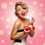 Happy Woman holding Gift Box. Pink background Royalty Free Stock Photo