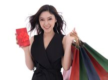 Happy woman holding gift box and shopping bag isolated on a whit. Young happy woman holding gift box and shopping bag isolated on a white background royalty free stock image