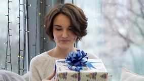 Happy woman holding gift boxes with Merry Christmas decoration in window background. Close up of woman holding gifts royalty free stock photo