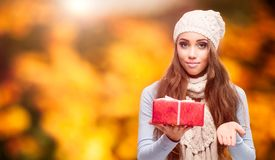 Happy woman holding gift over autumn background. Happy smiling young woman holding gift over autumn background Royalty Free Stock Images