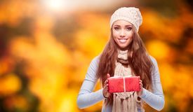 Happy woman holding gift over autumn background. Happy smiling young woman holding gift over autumn background Royalty Free Stock Photos