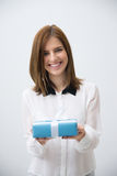Happy woman holding gift. Over gray background Royalty Free Stock Photography