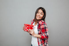 Happy woman holding gift over grey wall Royalty Free Stock Photography